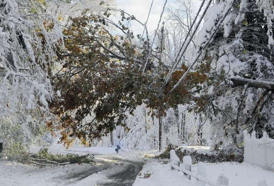 FILE -- In this Oct. 30, 2011 file photo, a man walks near a tree down on a power line a day after a snow storm in Glastonbury, Conn. Global warming is rapidly turning America into a stormy and dangerous place, with rising seas and disasters upending lives from flood-stricken Florida to the wildfire-ravaged West, the National Climate Assessment concluded Tuesday, May 6, 2014. (AP Photo/Jessica Hill, File)