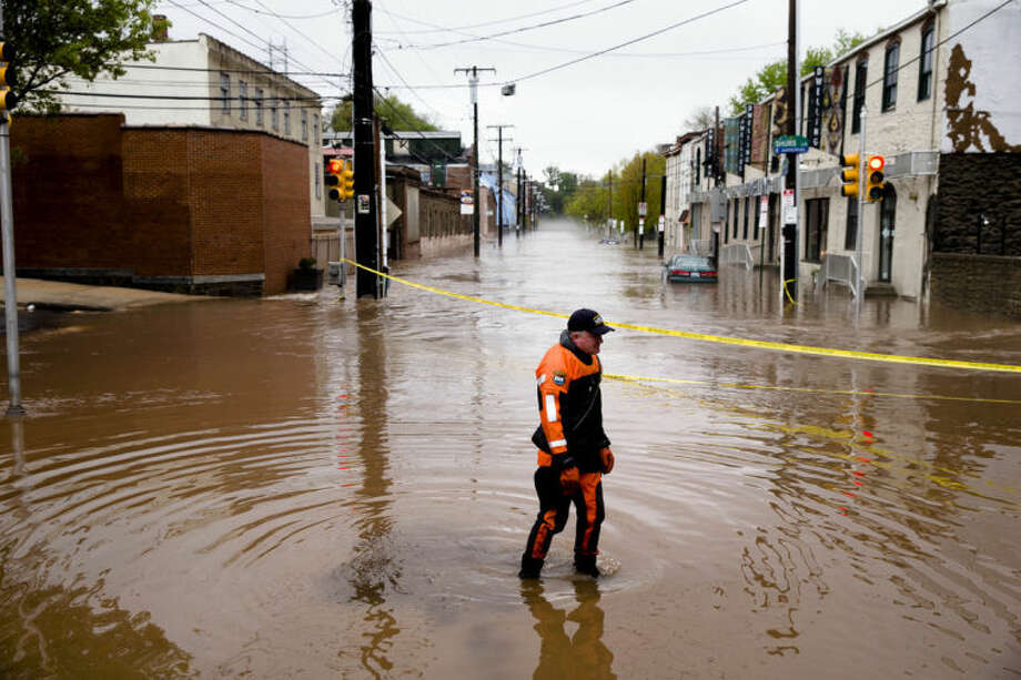 In this May 1, 2014 file photo, Marine unit police officer Robert Jonah walks through flood waters from the Schuylkill River on Main Street, Thursday, May 1, 2014, in the Manayunk neighborhood of Philadelphia. Global warming is rapidly turning America into a stormy and dangerous place, with rising seas and disasters upending lives from flood-stricken Florida to the wildfire-ravaged West, the National Climate Assessment report concluded Tuesday, May 6, 2014. (AP Photo/Matt Rourke)