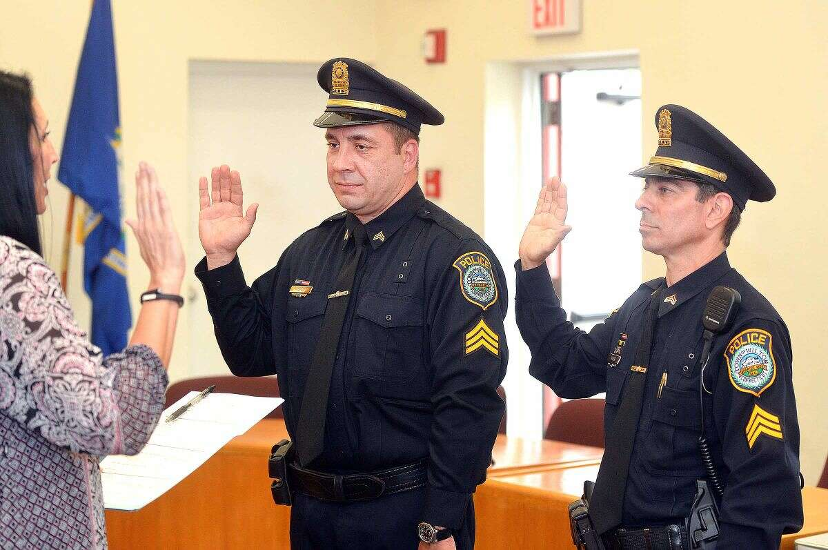 Wilton Town Clerk Lori Kaback instructs Wilton officers Anthony Cocco and Arnault Baker to raise their right hand as they are promoted to sergeant.