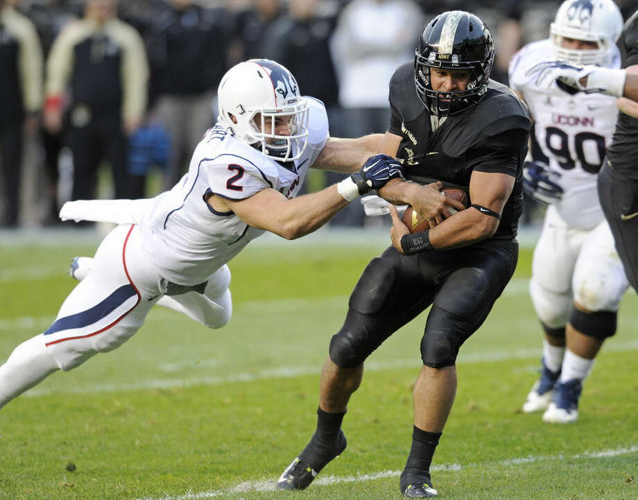Army quarterback Angel Santiago (3) protects the ball as he is tackled by Connecticut linebacker Graham Stewart during the first half of a college football game Saturday, Nov. 8, 2014, at Yankee Stadium in New York. (AP Photo/Bill Kostroun)