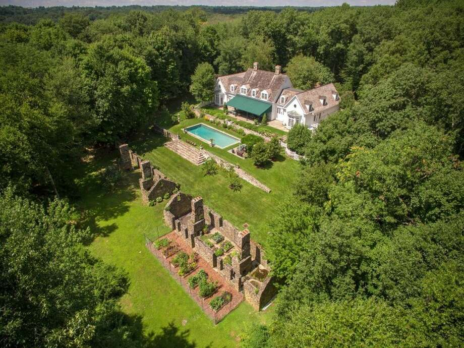 42 Lower Cross Rd, Greenwich, CT 06831 - 7 beds 6.5 baths 6,123 sqft; Features:Vestiges of the original stone farm structures, living room with French doors opens to terrace overlooking swimming pool,expansive terrace, rugged stone walls, manicured lawns, mature trees