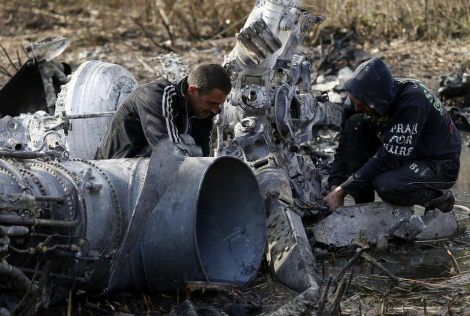 Local citizens collect parts of a downed Ukrainian military helicopter near a small town Raigorodok, outside Slovyansk, Ukraine, Tuesday, May 6, 2014. The helicopter was forced to make an emergency landing Monday during intense fighting in Slovyansk and was later destroyed by Ukrainian troops, who sought to ensure it did not fall into the hands of insurgent forces. (AP Photo/Darko Vojinovic)