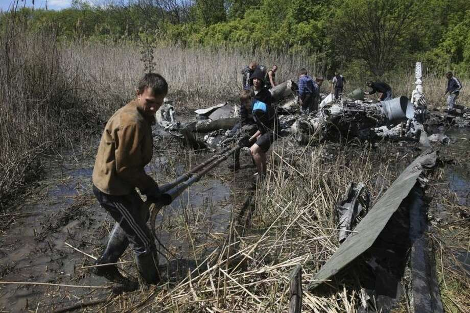 Local citizens collect parts of a downed Ukrainian military helicopter near a small town Raigorodok, outside Slovyansk, Ukraine, Tuesday, May 6, 2014. The helicopter was forced to make an emergency landing Monday during intense fighting in Slovyansk and was later destroyed by Ukrainian troops, who sought to ensure it did not fall into the hands of insurgent forces. (AP Photo)