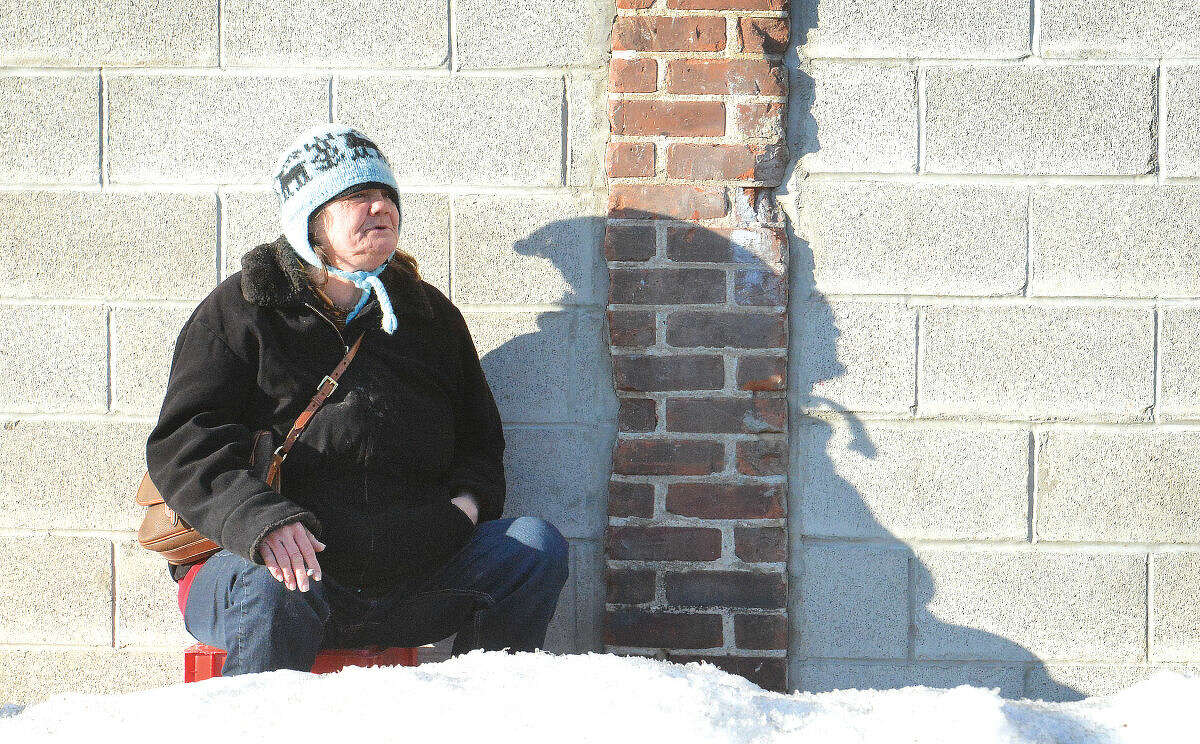 Hour Photo/Alex von Kleydorff Sarah sits on a milk crate and finishes a cigarette in the late afternoon sun on Merritt St. before she heads into The Open Door Shelter for the evening during record breaking cold weather in Norwalk during the winter.