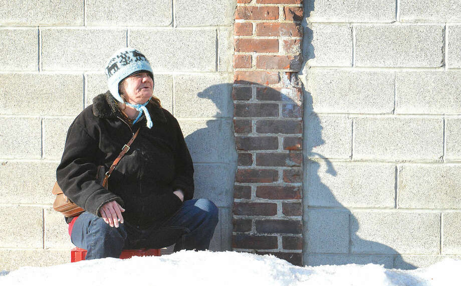 Hour Photo/Alex von KleydorffSarah sits on a milk crate and finishes a cigarette in the late afternoon sun on Merritt St. before she heads into The Open Door Shelter for the evening during record breaking cold weather in Norwalk during the winter.