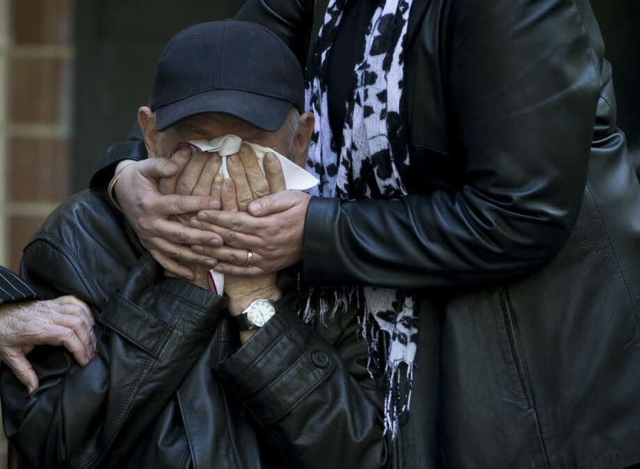 An elderly relative is comforted as the coffin of 17 year-old Vadim Papura is brought outside the apartment block he lived in, in Odessa, Ukraine, Tuesday, May 6, 2014. Papura died after jumping out of the burning trade union building in an attempt to escape Friday's fire that killed most of the 40 people that died after riots erupted last Friday. (AP Photo/Vadim Ghirda)