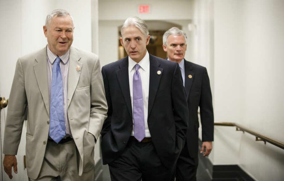 Rep. Trey Gowdy, R-S.C., center, speaks with Rep. Dana Rohrabacher, R-Calif., left, with Rep. Bob Latta, R-Ohio, right, as they walk to a House Republican Conference meeting at the Capitol in Washington, Wednesday, May 7, 2014. Speaker of the House John Boehner has tapped Gowdy, a former federal prosecutor, to chair a special select committee to investigate the attack on the U.S. diplomatic outpost in Benghazi, Libya, that killed the ambassador and three other Americans. Benghazi resonates with Republicans and remains a rallying cry with conservatives whose votes are crucial to the GOP in November's historically low-turnout midterm elections. (AP Photo/J. Scott Applewhite)