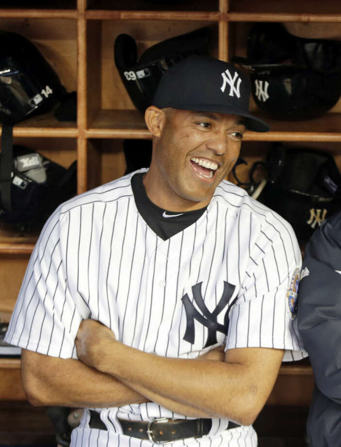FILE - In this Sept. 24, 2013, file photo, New York Yankees relief pitcher Mariano Rivera, left, talks to manager Joe Girardi in the dugout before a baseball game against the Tampa Bay Rays in New York. Rivera says he would take Boston's Dustin Pedroia over former teammate Robinson Cano as his top second baseman in his new book published Tuesday, May 6, 2014. (AP Photo/Kathy Willens, File)