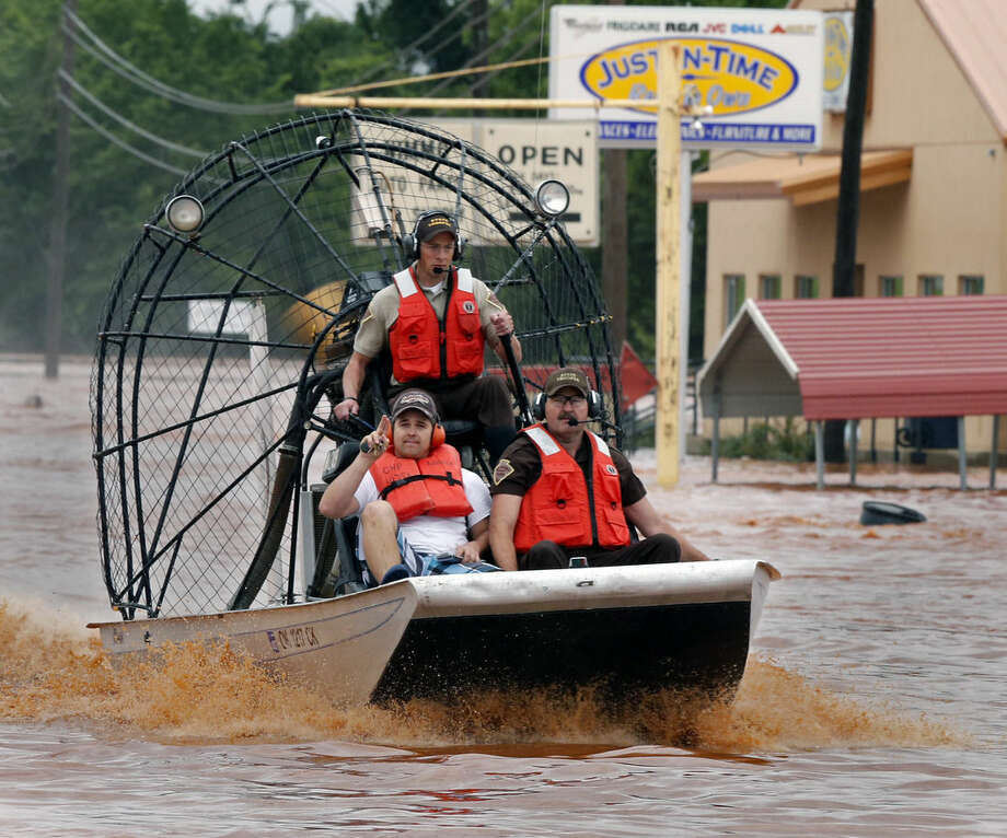 Highway patrolmen rescue Justin Nimmo, left, from his business, Just-In-Time, after flooding caused by rising water from Saturday night's storms trapped him in the store on Sunday, May 24, 2015 in Purcell, Okla. (Steve Sisney/The Oklahoman via AP) LOCAL STATIONS OUT (KFOR, KOCO, KWTV, KOKH, KAUT OUT); LOCAL WEBSITES OUT; LOCAL PRINT OUT (EDMOND SUN OUT, OKLAHOMA GAZETTE OUT) TABLOIDS OUT