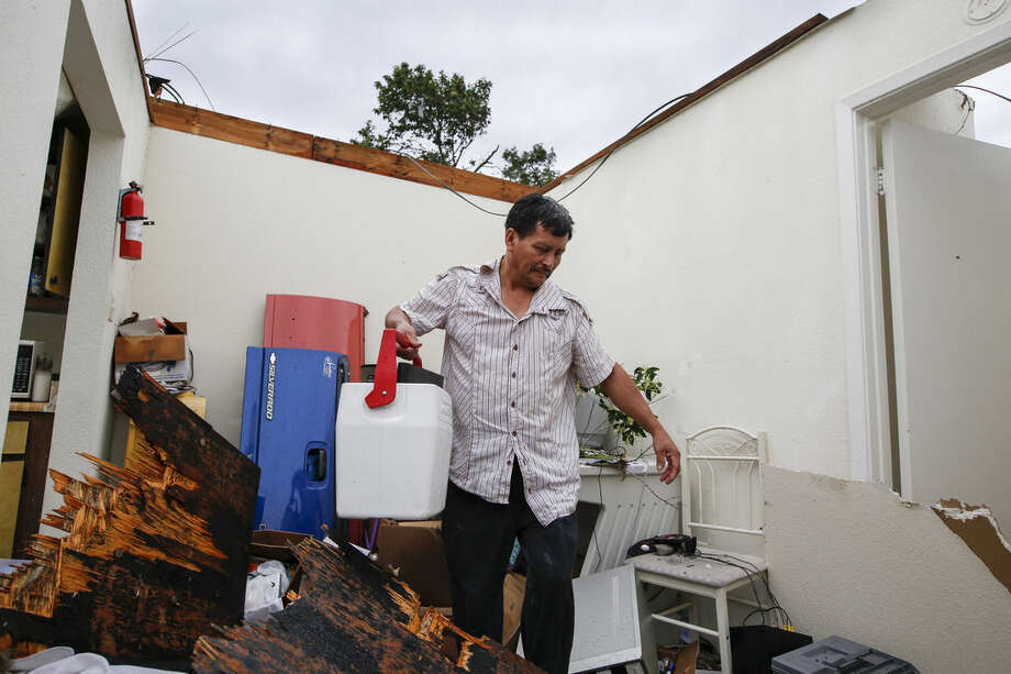 Mario Mai, who has lived at the complex for just over three years, collects some of his belongings in his apartment following a roof collapse during a morning storm, Sunday, May 24, 2015 in Houston at the Rockport Apartment Homes on S. Gessner. (Eric Kayne/Houston Chronicle via AP)