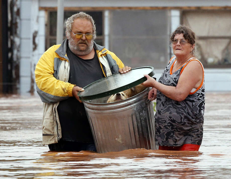 George and Susan Kruger make one of three trips with their animals from their flooded house to safety on Sunday, May 24, 2015 in Purcell, Okla. Rising water from overnight rains began to rise early in the morning. The Krugers refused to leave their home and made several trips to retrieve five dogs and a baby chick. (Steve Sisney/The Oklahoman via AP) LOCAL STATIONS OUT (KFOR, KOCO, KWTV, KOKH, KAUT OUT); LOCAL WEBSITES OUT; LOCAL PRINT OUT (EDMOND SUN OUT, OKLAHOMA GAZETTE OUT) TABLOIDS OUT