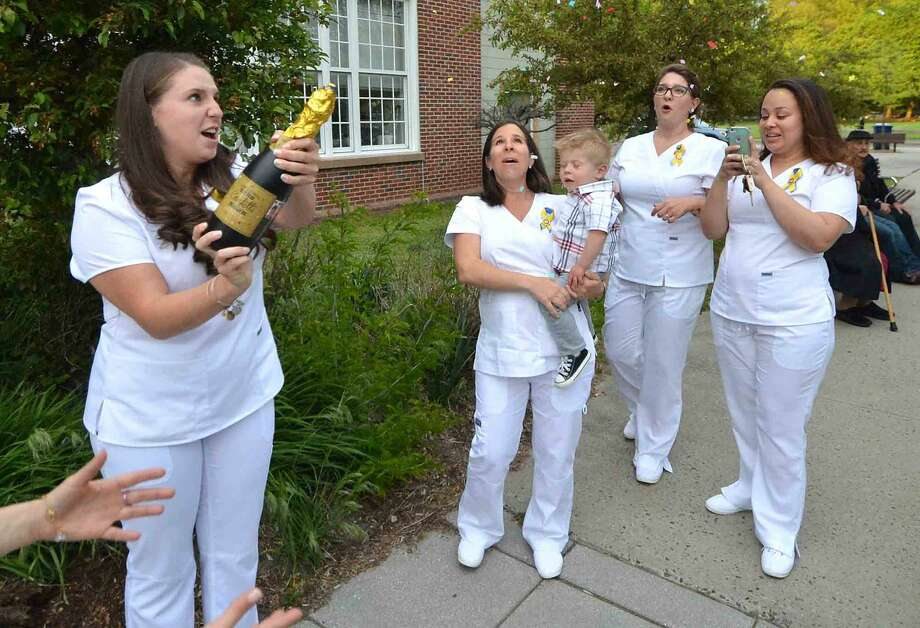 Graduate Jeanette Marrocco from Easton, opens some Confetti in a bottle after the Norwalk Community College Nursing Class of 2016 Pinning Ceremony at City Hall in Norwalk Conn. Tuesday May 17, 2016
