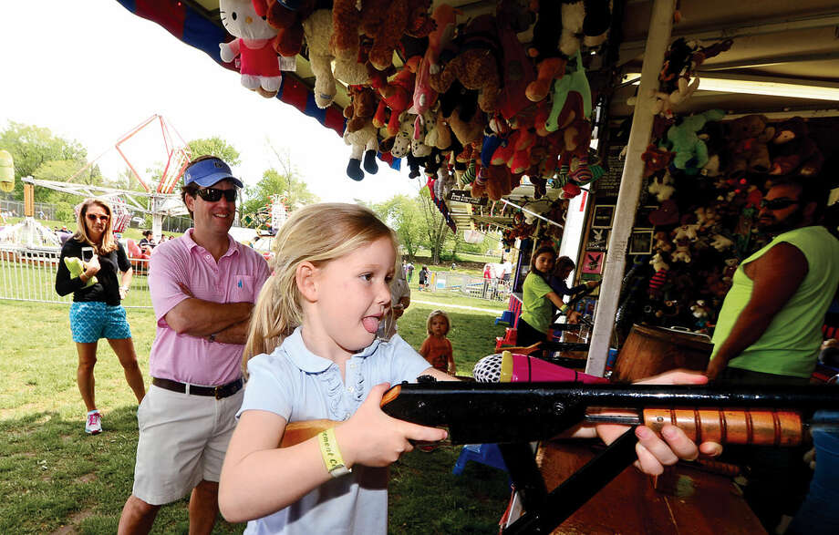 Chris Foster watches his daughter, Gray Foster, 5, shoot for a prize during the 25th annual Rowayton School Carnival Saturday May 14, 2016 at Rowayton Elementary School in Norwalk, Conn. The carnival is one of the top fundraisers for the school and all proceeds from the event support enrichment programs and educational technologies at the school.