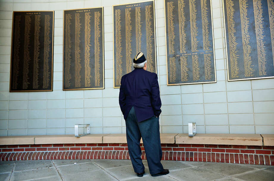 Hour photo / Erik Trautmann Charlie Williams, Chaplain for the Norwalk Veterans Memorial Committee looks over the names on the Veteran's Plaque as the city and the Veteran's Memorial Committee announced criteria for soliciting of names of residents to be placed on the Veterans' Plaque outside City Hall during a press conference Wednesday.
