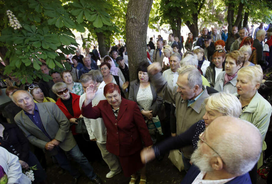People shout slogans during a commemoration service of four people killed during clashes last week between Ukrainian and pre-Russian forces, in the centre of Slovyansk, eastern Ukraine, Wednesday, May 7, 2014. The U.S. and European nations have increased diplomatic efforts ahead of Ukraine's May 25 presidential election, as a pro-Russian insurgency continues to rock the country's eastern regions. (AP Photo/Darko Vojinovic)