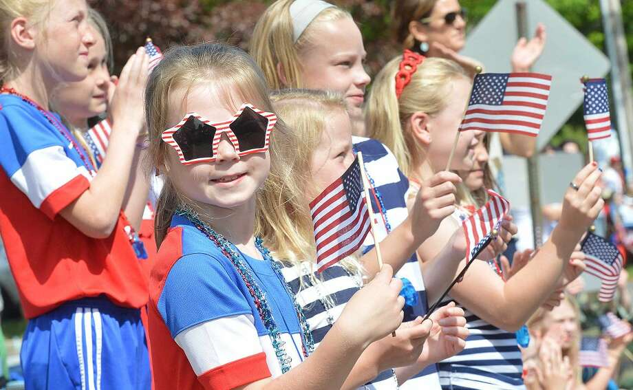 Hour Photo/Alex von Kleydorff Grace Ratcliffe and her friends wave flags as the parade passes during Wilton's Memorial day celebration