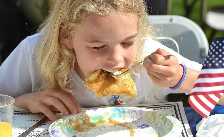 Hour Photo/Alex von Kleydorff 8yr old Kate lane digs into pancakes during the Kiwanis Pancake breakfast at The Wilton Congregational Church before the parade on Memorial day