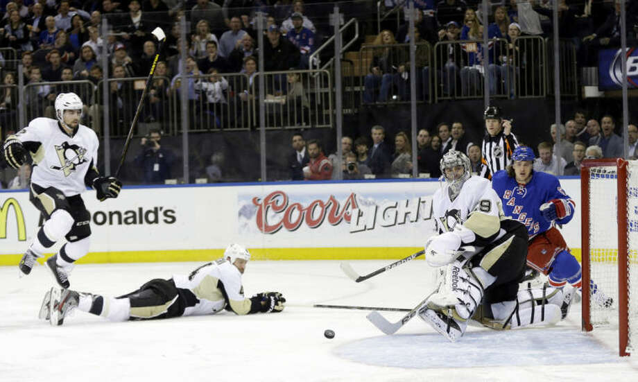 Pittsburgh Penguins goalie Marc-Andre Fleury (29), Rob Scuderi (4) and Matt Niskanen (2) look at the puck shot by New York Rangers' Carl Hagelin (62) for a goal during the second period of a second-round NHL Stanley Cup hockey playoff series Wednesday, May 7, 2014, in New York. (AP Photo/Frank Franklin II)