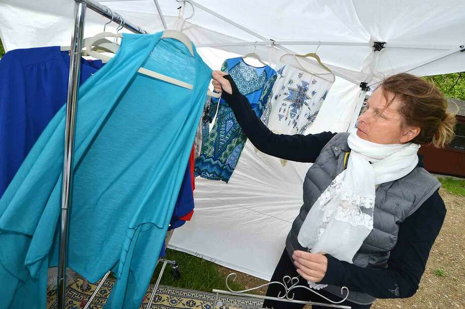 Wilton's Marie Wendorff moves some blouses and sweaters from the rack at her Witchy Poo booth at the Cannondale Spring Craft Festival in Cannondale Village in Wilton Conn. May 15, 2016