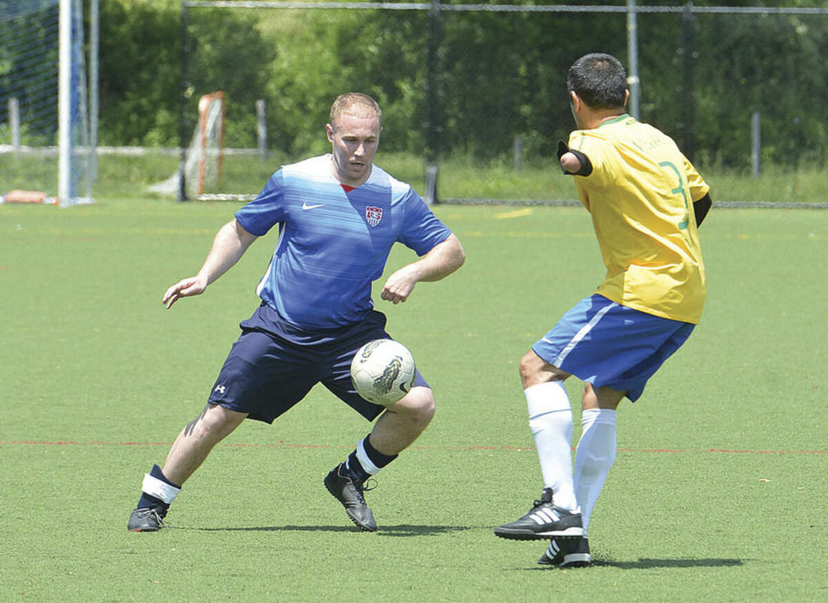 Hour photo/Alex von Kleydorff Wilton Blue's Tom Thresher, left, makes a move against the Ancient Warriors during Monday's game in the ninth annual Memorial Soccer Challenge to benefit Kick For Nick at Lilly Field in Wilton.