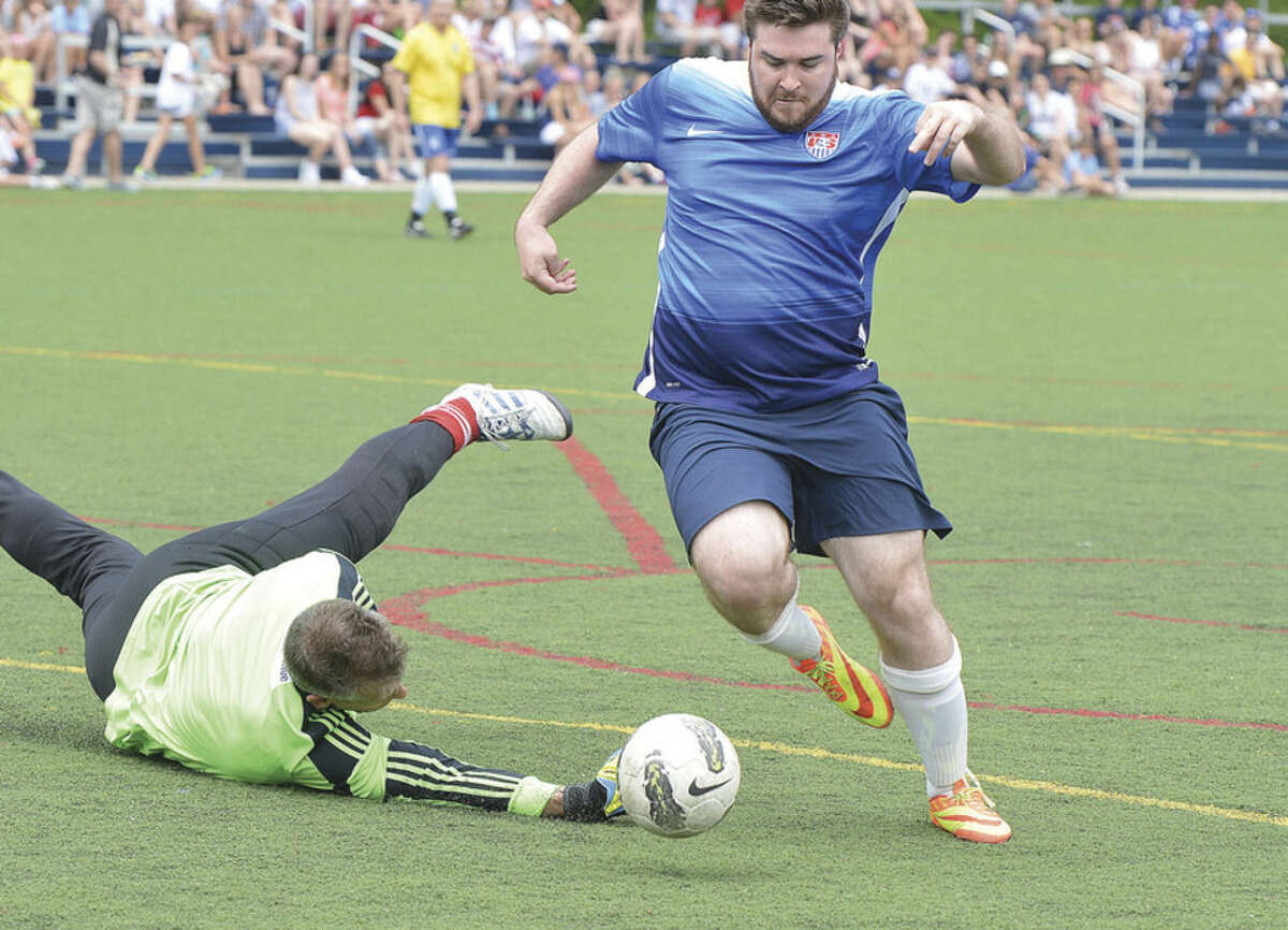 Hour photo/Alex von Kleydorff Wilton Blue's Tom Conley, right, gets past the Ancient Warriors' goalie on his way to scoring a goal during Monday's game in the ninth annual Memorial Soccer Challenge event at Lilly Field in Wilton.