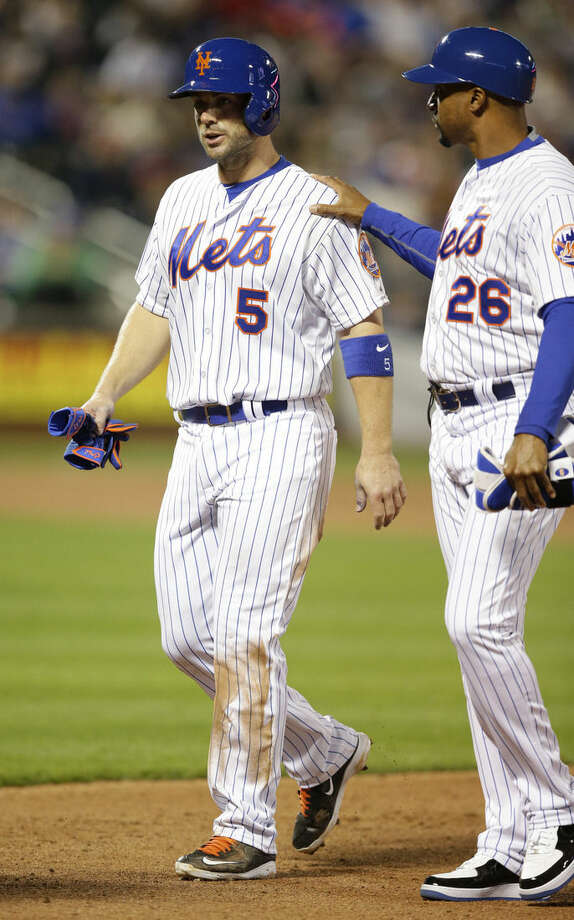 FILE - In this April 14, 2015, file photo,New York Mets first base coach Tom Goodwin (26) consoles Mets David Wright (5) who left the field in the eighth inning of a baseball game against the Philadelphia Phillies in New York. Mets third baseman David Wright has been sent to California to work with the staff of back specialist Dr. Michael Watkins. Wright hasn't played since pulling his right hamstring against Philadelphia on April 14. His rehabilitation was put on hold May 6 when back pain developed. (AP Photo/Kathy Willens, File)