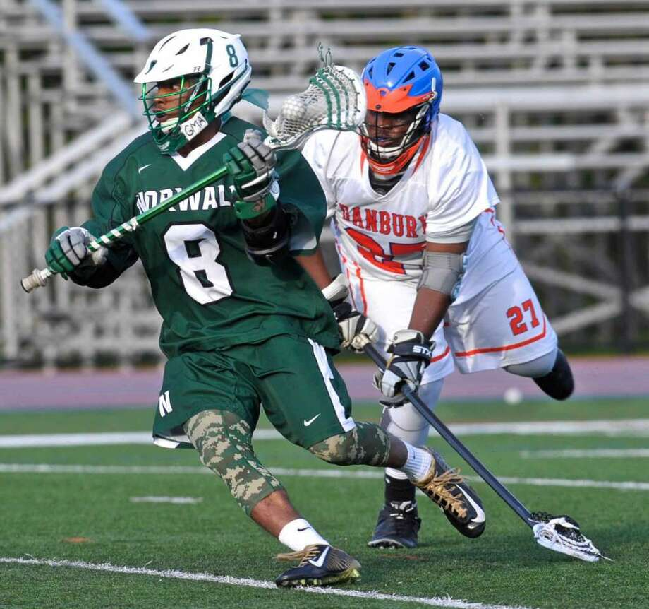 Norwalk's Dakari Eason (8) goes past Danbury's Soloman James (27) in the boys lacrosse game between Norwalk and Danbury high schools, on Tuesday, May 17, 2016, at Danbury High School, Danbury, Conn.