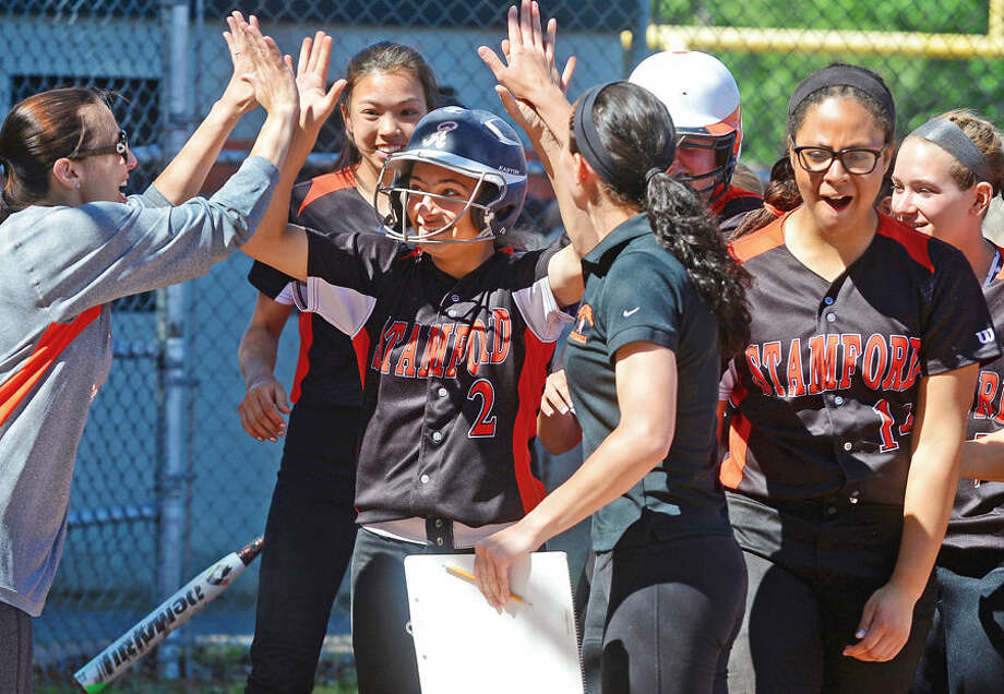 Hour photo / Erik Trautmann #3 for Stamford Maddie Santora is congratulated after hitting a home run against Norwalk during their FCIAC semi-final game in Stamford Saturday.
