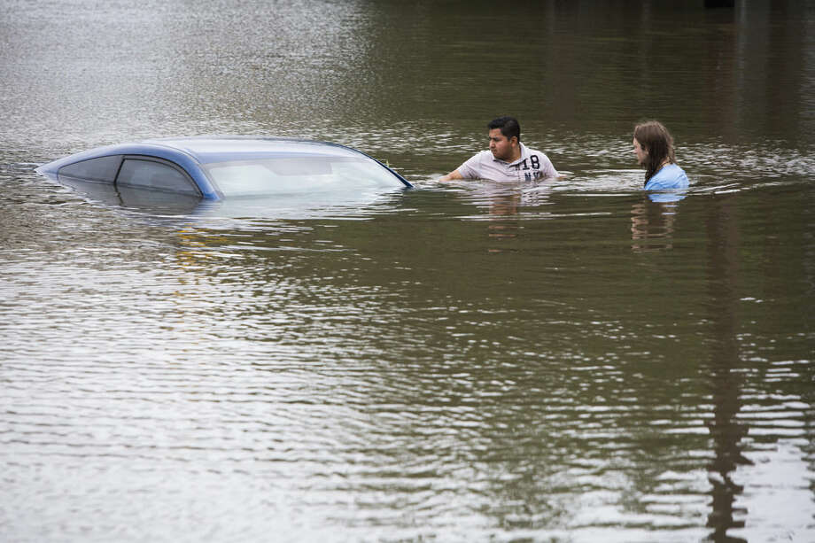 Roberto Salas, left, and Lewis Sternhagen, right, check a flooded car on the frontage road in between South Loop West Freeway and South Post Oak Road near the Willow Waterhole Bayou, Tuesday, May 26, 2015, in Houston. Floodwaters kept rising Tuesday across much of Texas as storms dumped almost another foot of rain on the Houston area, stranding hundreds of motorists and inundating the highways. (Marie D. De Jesus/Houston Chronicle via AP)