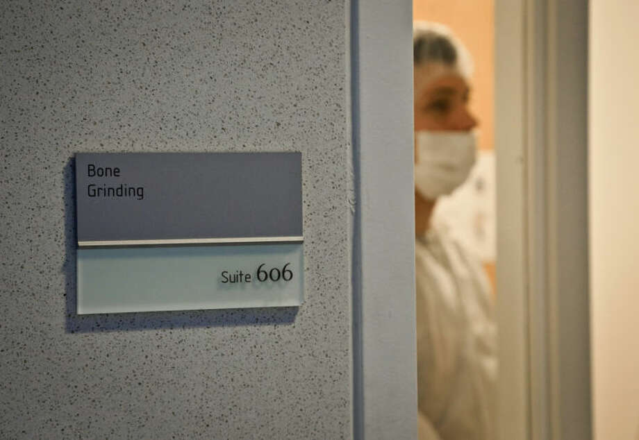 In this April 15, 2014 photo, Michael Mosco, a criminalist, prepares to enter the bone grinding room at the Office of Chief Medical Examiner in New York. The room is central to the examination of bone DNA from those who died on Sept. 11, 2001. Forensic scientists are still trying to match the bone with DNA from victims who have never been identified. The resting place for thousands of vacuum-sealed plastic pouches with remains of the victims are to be moved to the new trade center site Saturday, May 10. (AP Photo/Bebeto Matthews)