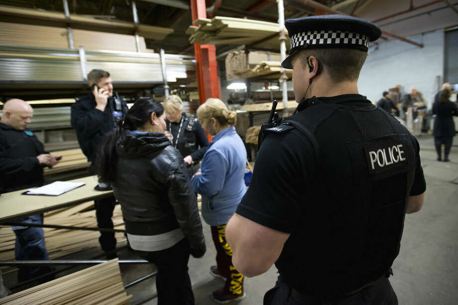 In this Dec. 15, 2014 photo, a police officer looks on as interviews are conducted with factory workers after Greater Manchester Police officers alongside partner agency teams from Rochdale Council, the Home Office and Her Majesty's Revenue and Customs, raided a picture framing factory in Rochdale, Northern England, investigating trafficking for sham marriages. Dozens of women from the poorer corners of eastern Europe are lured each year to the West for such marriages with men who want to gain the right to live, work or claim benefits in Europe. (AP Photo/Jon Super)