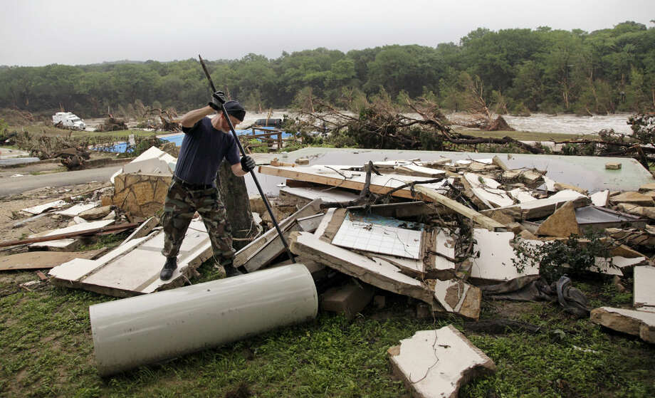 Kevin Calaway pries apart debris from a cabin shattered from a flood days earlier at a resort along the Blanco River, Tuesday, May 26, 2015, in Wimberley, Texas. Recovery teams were searching for as many as 12 members of two families who are missing after a rain-swollen river in Central Texas carried a vacation home off its foundation, slamming it into a bridge downstream. The hunt for the missing picked up after a holiday weekend of terrible storms that dumped record rainfall on the Plains and Midwest, caused major flooding and spawned tornadoes and killed at least eight people in Oklahoma and Texas. (AP Photo/Elaine Thompson)