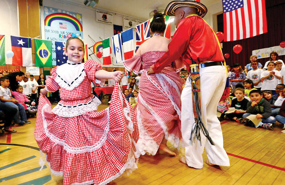 "Student Valeria Antunes dances with traditional Colombian dancers during Columbus Magnet School's 11th annual ""Rainbow of Cultures'"" second-grade culture fair Tuesday May 17 2016 at the school. Each year second graders prepare presentations to show the diversity of their cultural heritage."
