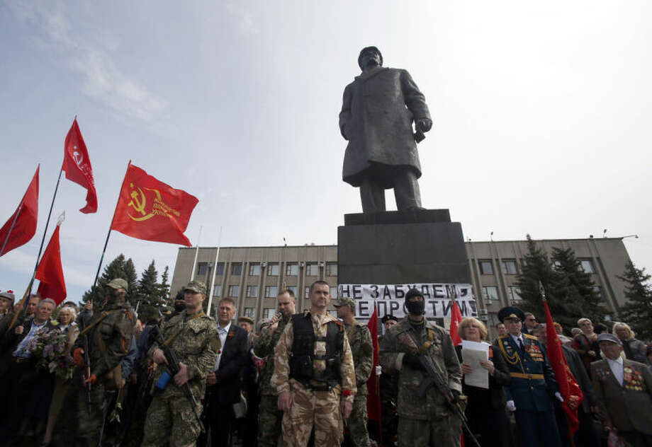Pro-Russian gunmen stand guard in front of the monument of Soviet Union founder Vladimir Lenin, during a Victory Day celebration, which commemorates the 1945 defeat of Nazi Germany, in the center of Slovyansk, eastern Ukraine, Friday, May 9, 2014. Putin's surprise call on Wednesday for delaying the referendum in eastern Ukraine appeared to reflect Russia's desire to distance itself from the separatists as it bargains with the West over a settlement to the Ukrainian crisis. But insurgents in the Russian-speaking east defied Putin's call and said they would go ahead with the referendum. (AP Photo/Darko Vojinovic)