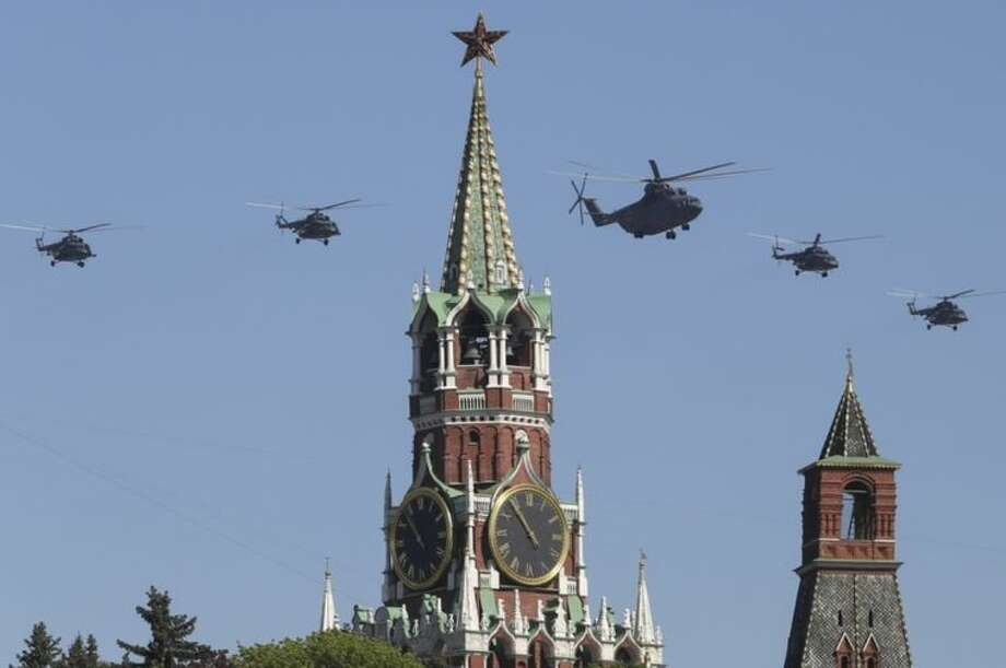 Russian Air Force helicopter Mi-26, center, with Mi-8, flies over Red Square during a Victory Day parade, which commemorates the 1945 defeat of Nazi Germany, in Moscow, Russia, Friday, May 9, 2014. Russia marked the Victory Day on May 9 holding a military parade at Red Square. (AP Photo/Denis Tyrin)