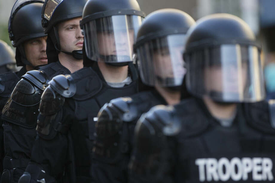 FILE - In this May 23, 2015, file photo, riot police stand in formation as a protest forms against the acquittal of Michael Brelo, a patrolman charged in the shooting deaths of two unarmed suspects in Cleveland. The city of Cleveland has reached a settlement with the U.S. Justice Department over a pattern of excessive force and civil rights violations by its police department, and the agreement could be announced as soon as Tuesday, May 26, 2015, a senior federal law enforcement official said. (AP Photo/John Minchillo, File)