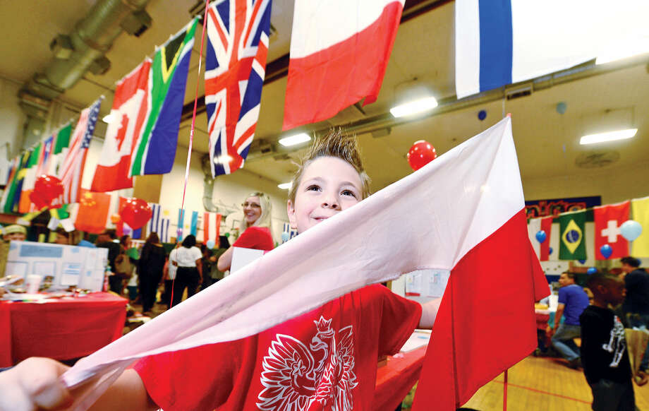"Student presenter Dawid Shadyk holds the Polish flag during Columbus Magnet School's 11th annual ""Rainbow of Cultures'"" second-grade culture fair Tuesday May 17 2016 at the school."