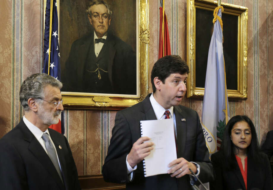 U.S. Attorney Steven Dettelbach, center, holds up the settlement agreement with the City of Cleveland as he speaks at a news conference Tuesday, May 26, 2015, in Cleveland. Cleveland agreed to overhaul its police department under the supervision of a federal monitor in a settlement announced Tuesday with the U.S. Department of Justice over a pattern of excessive force and other abuses by officers. The announcement comes three days after a white patrolman was acquitted of voluntary manslaughter charges in the shooting deaths of two unarmed black suspects in a 137-shot barrage of police gunfire following a high-speed chase. The case helped prompt an 18-month investigation by the Justice Department. Cleveland Mayor Frank Jackson, left, and Vanita Gupta, head of civil rights division at the Department of Justice, right, listen. (AP Photo/Tony Dejak)