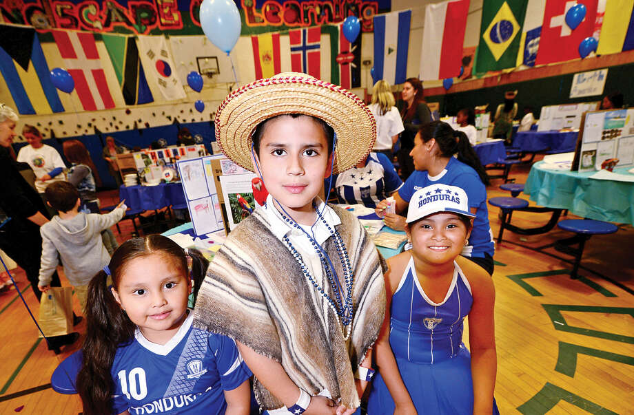 "Presenters Brian Tapia and Perla Alpantara pose with Perla's sister, left, Kindergartner Alonia Alpantara during Columbus Magnet School's 11th annual ""Rainbow of Cultures'"" second-grade culture fair Tuesday May 17 2016 at the school."