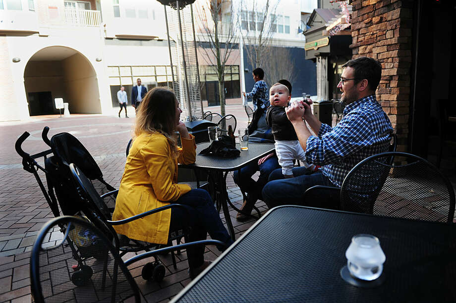 Sarah and Chris McDougal dine with their son Caden, seven months, at Sedona Taphouse at Pointe Place Market which is part of many new apartment buildings, businesses and ongoing construction projects which greet people who exit I95 onto West Avenue in Norwalk, Conn., on Friday Apr. 1, 2016. The McDougal's just moved into one of the new apartments in the complex.