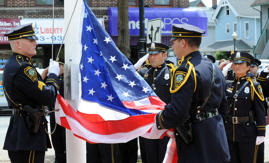 Sgt.Shannon Sherry and Officer Christopher Wasilewski raise the American flag at the annual Norwalk Police Department Memorial held on Wednesday, May 18, 2016 at police headquarters in Norwalk, Conn. The service was held as part of national police week to honor the memory of fellow officers who have lost their lives in the service as well as those lost to suicide.