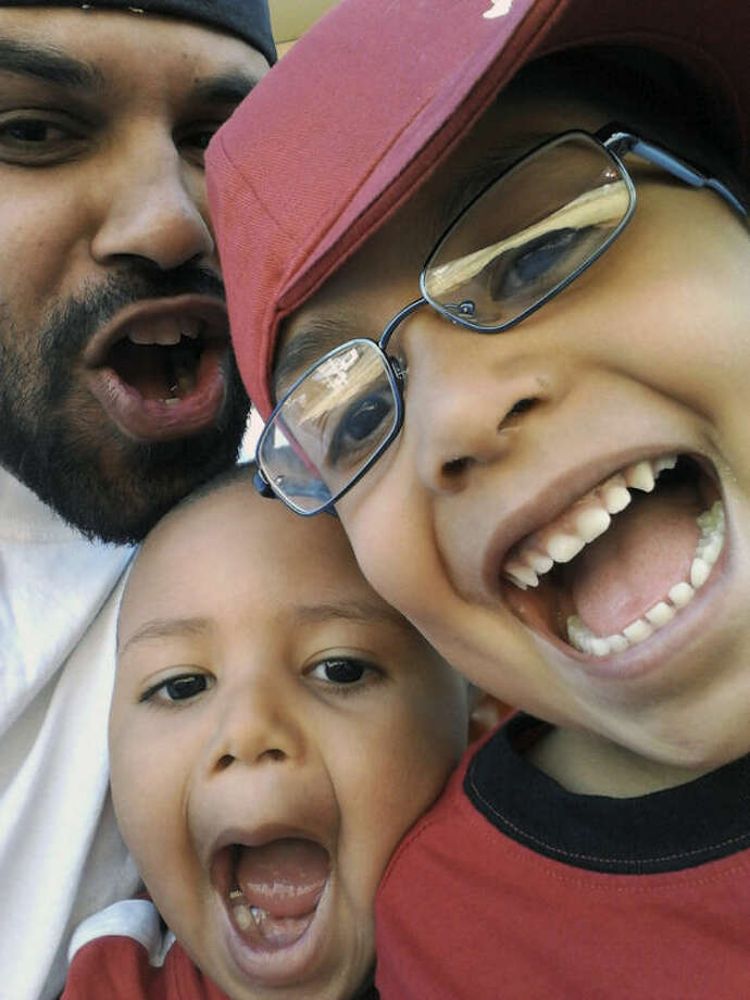 In this undated photo provided by the the Lima-Marin Family, Rene Lima-Marin jokes around with children Justus, 7, and Josiah, 4, in Aurora, Colo. Rene Lima-Marin was sentenced in 2000 for a conviction in a robbery, kidnapping and burglary after robbing two Aurora video stores when Marin was 18. Marin was to stay in prison the rest of his life and serve 98 years. He was released after just 8 years due to a clerical error, living a crime-free life for six years before being sent back after authorities discovered their mistake. (AP Photo/Lima-Marin Family)