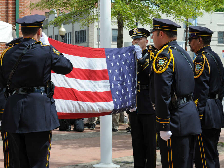 Officer Christopher Wasilewski and Sgt. Shannon Sherry fold the flag for presenation during the annual Norwalk Police Department Memorial held on Wednesday, May 18, 2016 at police headquarters in Norwalk, Conn. The service was held as part of national police week to honor the memory of fellow officers who have lost their lives in the service as well as those lost to suicide.