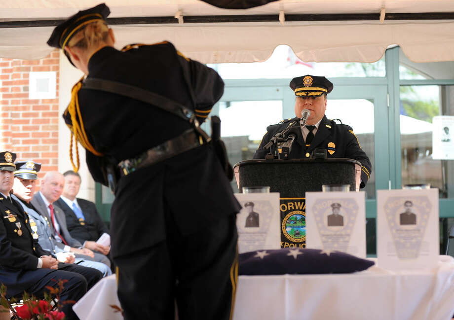 Deputy Chief Ashley Gonzalez reads the names aS Detective Kristina LaPak lights the candles at the annual Norwalk Police Department Memorial on Wednesday, May 18, 2016 at police headquarters in Norwalk, Conn. The service was held as part of national police week to honor the memory of fellow officers who have lost their lives in the service as well as those lost to suicide.