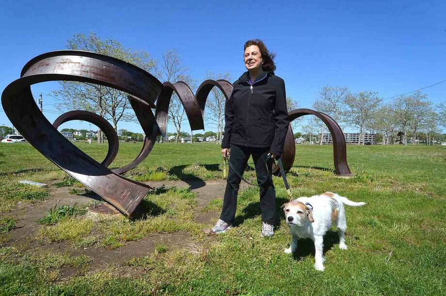 Weston artist Carole Eisner and her dog Chester with her Rolled I Beam sculpture 'Spring-A-Ling' on view at Veterans Park in Norwalk. This and others of hers from Vets Park are being moved to Prospect Park in Brooklyn, N.Y.. In Norwalk Conn. Monday May 16, 2016