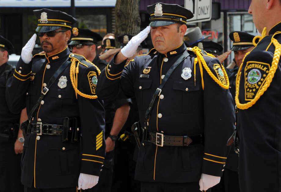 Officers Irving Bolling and David Neves salute the flag during the annual Norwalk Police Department Memorial on Wednesday, May 18, 2016. The service at police headquarters in Norwalk, Conn. was held as part of national police week to honor the memory of fellow officers who have lost their lives in the service as well as those lost to suicide.