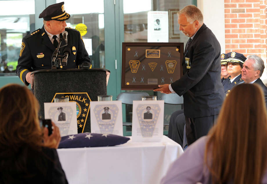 Retired Norwalk Police Officer Michael Price, right, presented Police Chief Thomas Kulhawik with a shadowbox that honors Norwalk officers who took their own lives during the annual Norwalk Police Department Memorial on Wednesday, May 18, 2016. The service at police headquarters in Norwalk, Conn. was held as part of national police week to honor the memory of fellow officers who have lost their lives in the service as well as those lost to suicide.
