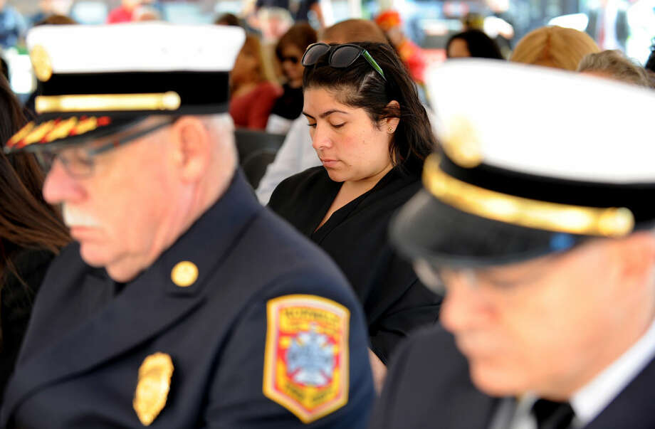 Marisol Carias, daughter of fallen officer Marco Carias, bows her head during a moment of silence at the annual Norwalk Police Department Memorial on Wednesday, May 18, 2016 at police headquarters in Norwalk, Conn. The service was held as part of national police week to honor the memory of fellow officers who have lost their lives in the service as well as those lost to suicide.