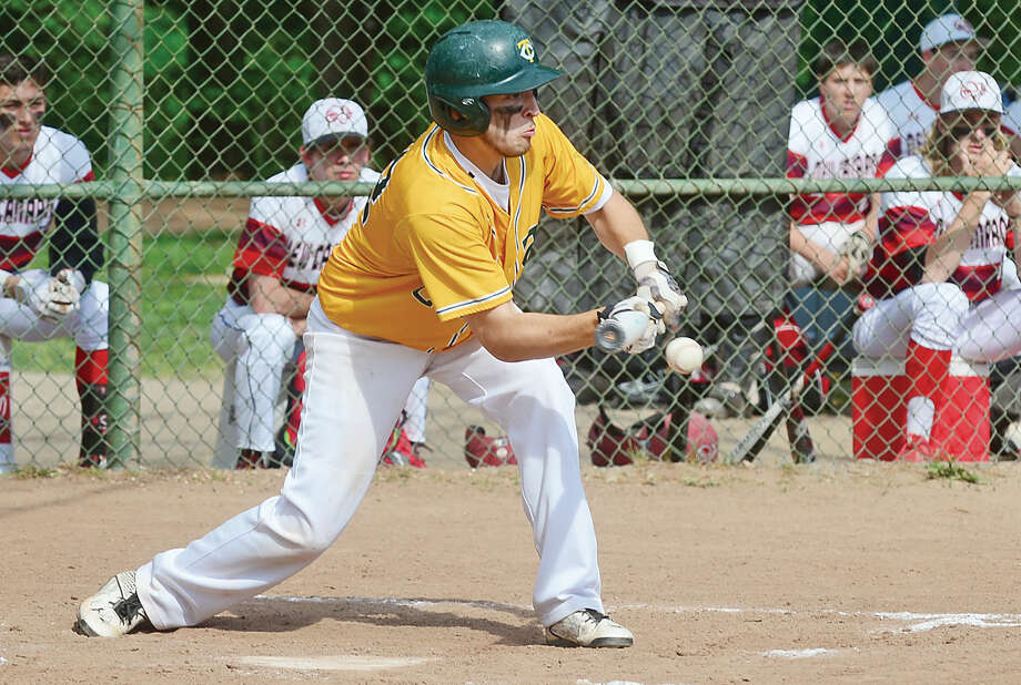Hour photo / Erik Trautmann Trinity Catholic's #22 Anthony Hoegemann bunts during their game against New Canaan Tuesday at Mea Park in New Canaan.