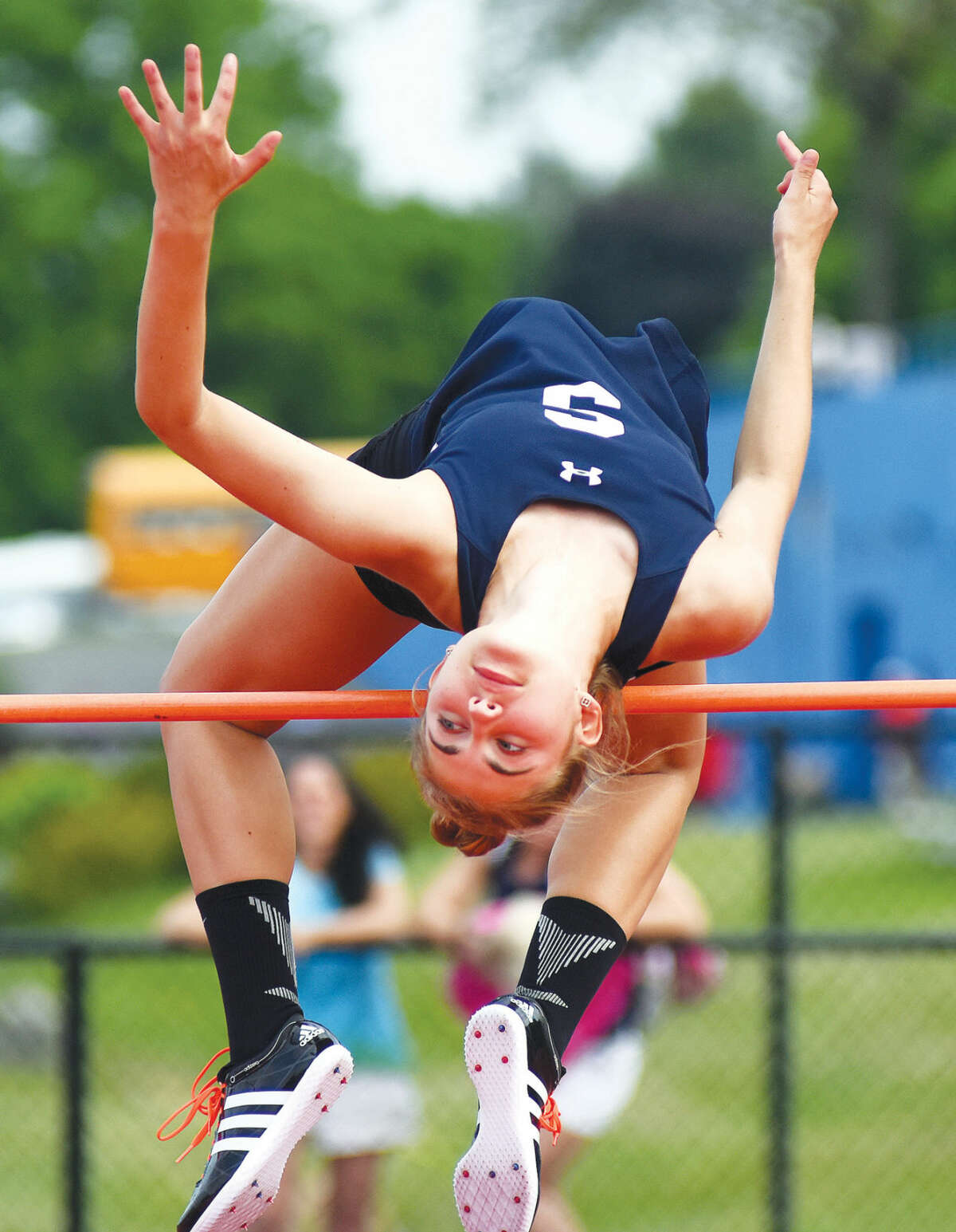 Hour photo/John Nash - Staples High School's Elizabeth Knoll arches herself over the high jump during Tuesday's FCIAC track and field championship meet in Danbury. Knoll won the event with a jump of 5-feet-6.